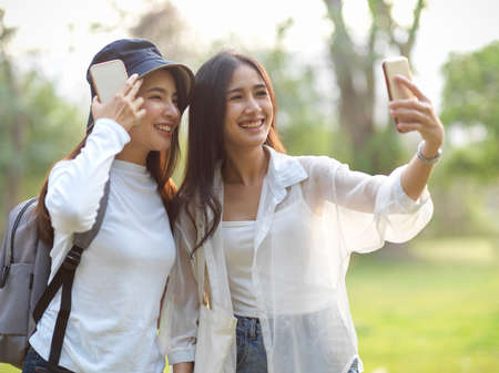 Portraits of two young female travellers taking photo with smartphone while walking around in the park Banque d'images