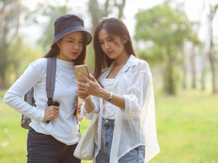 Quarter-length portraits of two young female travellers looking on smartphone while finding their destination Standard-Bild