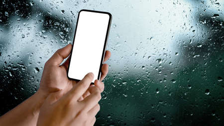 Close up view of male hands using mock-up smartphone in blurred raindrop on glass window background, clipping path 版權商用圖片