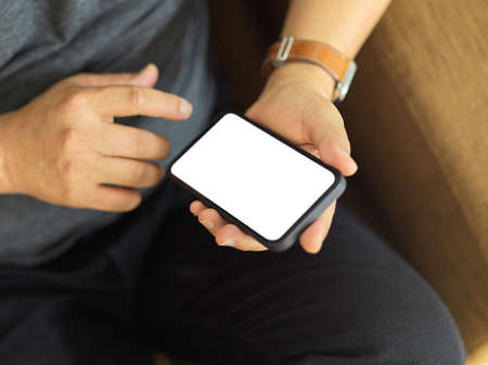 Top view of male hands using smartphone include clipping path screen while sitting on the couch
