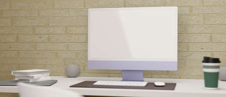Simple computer desk with monitor, keyboard, accessories and supplies on white table with brick wall, 3D rendering, 3D illustration 版權商用圖片
