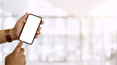 Close up view of hands using smartphone and showing mock-up screen to camera in blurred background, clipping path 版權商用圖片