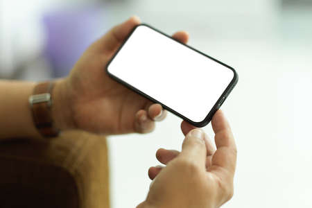 Cropped shot of male holding smartphone with horizontal mock-up screen in blurred background, clipping path