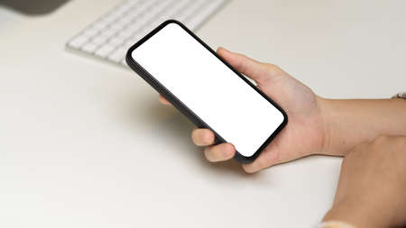 Side view of female hand holding smartphone with mock-up screen on computer desk, clipping path Standard-Bild