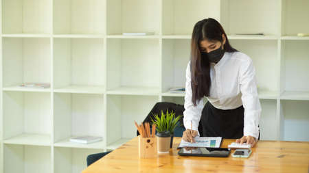 Female office worker with face mask working with paperwork in her office room 版權商用圖片