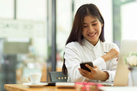 Portrait of female office worker using smartphone while relaxing from work in office room