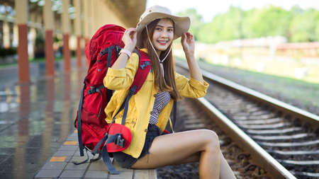 Side view of female backpacker smiling and pasting to camera while sitting at railway