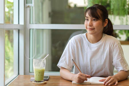 Portrait of friendly female teenager looking out of the window while doing home work in cafe 版權商用圖片
