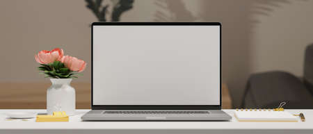 Computer laptop with mock-up screen on white table with stationery and flower vase, 3D rendering, 3D illustration 版權商用圖片