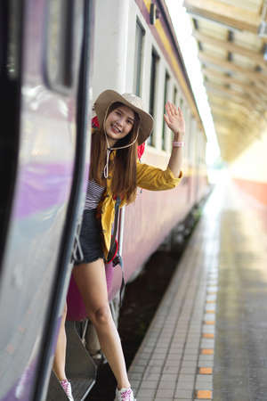 Young female backpacker stepping down of the train and smiling to celebrate her journey