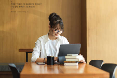 Portrait of young female student researching for her thesis with digital tablet and books in library 版權商用圖片