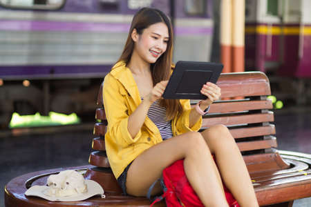 Young female backpacker using digital tablet to check her plan at train station