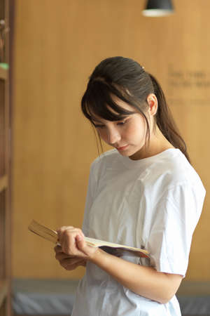 Portrait of young female student reading a book while searching book for her project in library