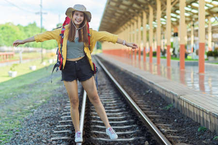 Full-length portrait of young female traveller walking on the railway, smiling and posting to camera