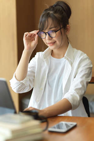 Young pretty female student with eyeglasses preparing for upcoming exam with digital tablet in cafe 版權商用圖片
