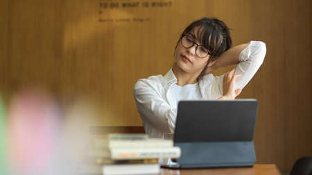 Young female student relaxing and stretching her neck while doing assignment in library 版權商用圖片