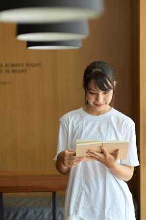 Quarter-length portrait of young female student reading a book while standing in library