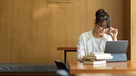 Young female student with eyeglasses research information for her thesis with books and digital tablet in library