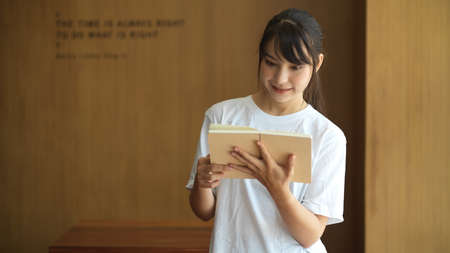 Half-length portrait of young female student reading a book while standing in library 版權商用圖片