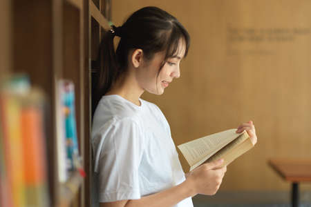 Side view of portrait of young female student reading a book while searching book in library