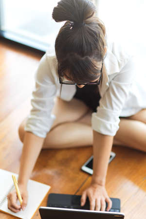 Top view of young female student doing home work with notebook and digital tablet on the floor in living room