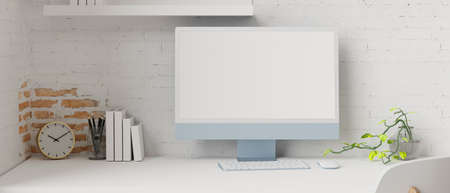 Computer monitor with mock-up screen in workspace with stationery, decorations and brick wall, 3D rendering, 3D illustration