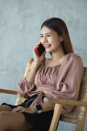 Portrait of female office worker talking on the phone while relaxed sitting in cafe 版權商用圖片