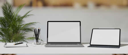 Laptop and digital tablet with mock-up screen on white table with stationery in blurred background, 3D rendering, 3D illustration 版權商用圖片