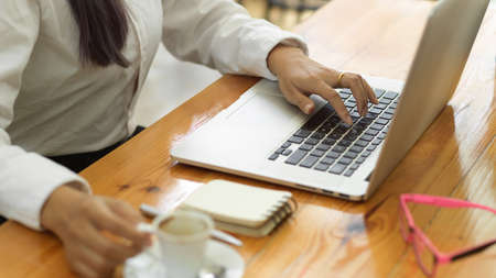 Side view of businessperson hand working with laptop and holding coffee cup on workspace