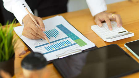 Close up view of businessperson hands working with paperwork and calculator on workspace 版權商用圖片