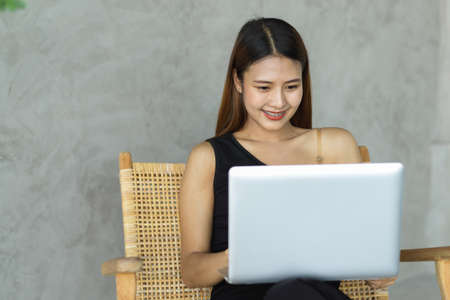 Portrait of young beautiful woman using laptop on her lap while relaxed sitting in leisure corner