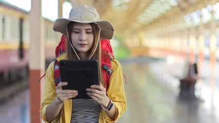 Portrait of female traveller holding digital tablet while working in platform at train station 版權商用圖片