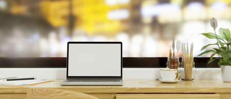 Laptop with mock-up screen on the table with paint tools and stationery beside the window, 3D rendering, 3D illustration