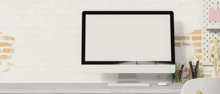 Computer monitor with mock-up screen on the desk with supplies and brick wall background, 3D rendering, 3D illustration