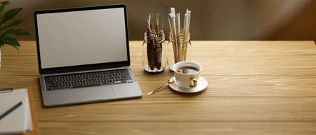 Laptop with mock-up screen on wooden table with paint tools and coffee cup, 3D rendering, 3D illustration 版權商用圖片