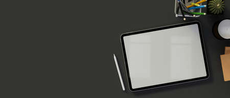Digital tablet with mock-up screen on dark table with supplies and copy space, 3D rendering, 3D illustration 版權商用圖片