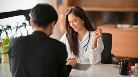 Cheerful asian female doctor discusses the medical treatment plan with male patient in examination room. Male patient make a follow-up appointment with a female physician. Foto de archivo