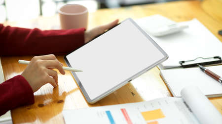 Cropped image of a smart young female financial worker estimating business financial flow at the office using a modern digital tablet and financial data papers. Фото со стока