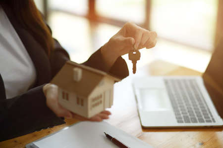 Cropped image of female realtor broker holding home keychain and house model in her hand, sits at the desk in office. Фото со стока