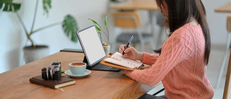 Side view of millennial female writing on her diary while looking at digital tablet computer, remotely working at cafe. tablet screen mockup