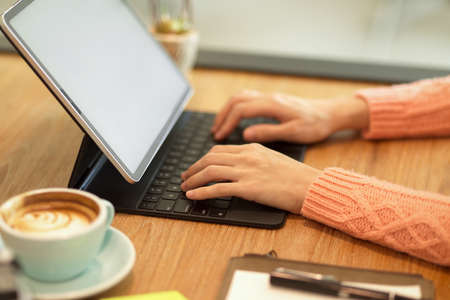 Close-up focus female hands in pink sweater at cafe typing on keyboard working on modern tablet computer, tablet blank screen mockup