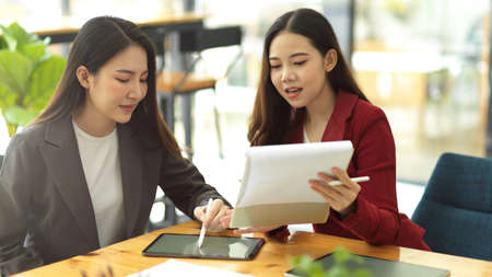 Young asian businesswomen meeting and brainstorming on their project together in modern office. Corporate works, teamwork concept. Фото со стока