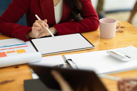 Executive professional asian businesswoman sits at her desk and work with digital tablet and financial papers. tablet screen mockup