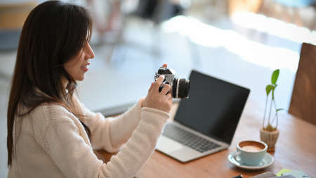 Beautiful young asian female freelancer photographer, web blogger looking a photo in camera at co-working space Фото со стока