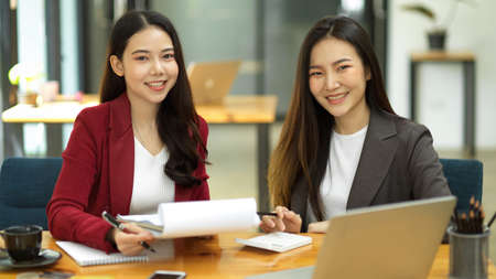 Happy and friendly attractive Asian businesswomen or accountants collaborate at their office desk.