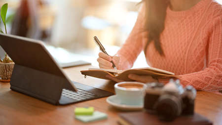 Cropped image Young female freelancer blogger influencer writing notes on her diary, sitting at restaurant. Фото со стока