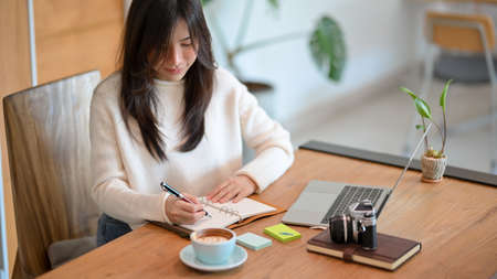 Young asian woman managing her work schedule in her personal diary, taking notes while working on laptop computer at office.