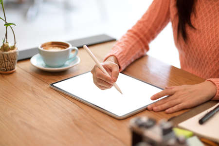 Close-up Female freelance graphic designer sketching her graphic digital photo art on modern tablet computer with stylus. tablet blank screen mockup