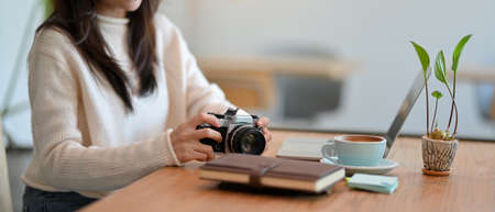 Cropped image of Female freelancer photo grapher with retro vintage camera, laptop and her stuff on table at coffee shop