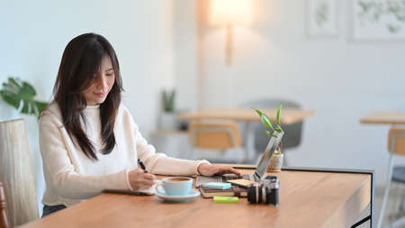 Pleased young asian female making a notes on her diary while working on laptop computer at minimalist cafe